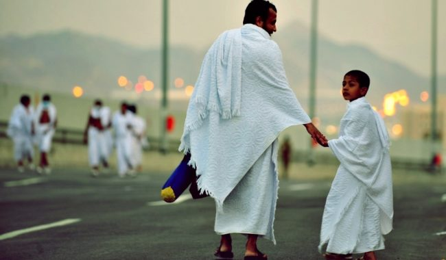 A Muslim pilgrim walks with his son along the road in the Mina valley five kilometres (three miles) east of the Saudi Arabian holy city of Mecca, on November 14, 2010, as some 2.5 million Muslim pilgrims descend on the holy city for the annual Hajj pilgrimage. The passage to Mina marks the official launch of the hajj on the eighth day of the Muslim calendar month of Dhul Hijja. The day is known as Tarwiah (Watering) as pilgrims in the past stopped at Mina to water their animals and stock up for the trip to Mount Arafat.  AFP PHOTO / MUSTAFA OZER (Photo credit should read MUSTAFA OZER/AFP/Getty Images)